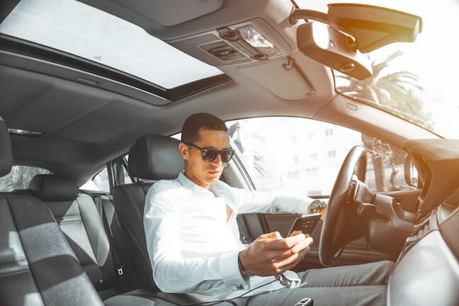 The Impact of Phone Use While Driving Man driving while using cell phone