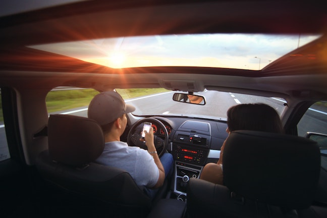 Couple driving while using cell phone, Driver using phone to navigate while driving.