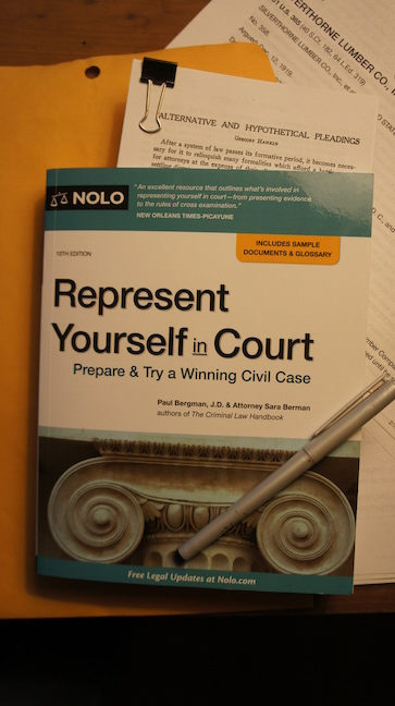 Represent yourself in court book on desk. Book by NOLO
