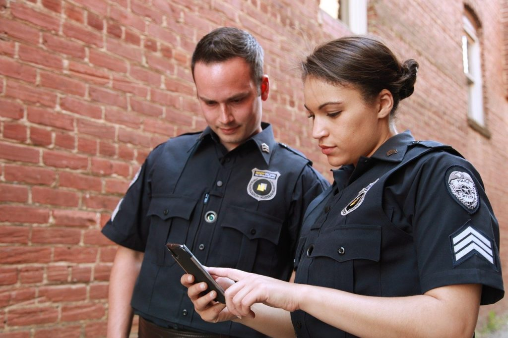 Police officers checking cell phone history of drivers